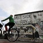 A woman cycles past a portion of the Berlin Wall on October 16, 2008 at the East Side Gallery in Berlin. The East Side Gallery, a more than one kilometre long section of the Wall decorated with paintings by international artists, is to be restored, as most of the paintings are badly damaged by erosion, graffiti and vandalism.     AFP PHOTO    BARBARA SAX        (Photo credit should read BARBARA SAX/AFP/Getty Images)